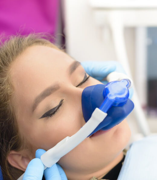 A woman with a nitrous oxide mask on.
